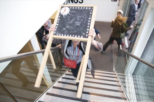 A player runs up some stairs carrying a blackboard.