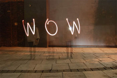 Long-exposure photograph showing an indeterminate figure in front of a wall, writing 'wow' with a torch.