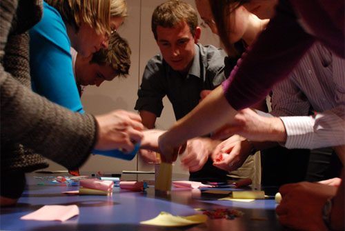A group crowds around a table, constructing a tower of post-it notes and paperclips.