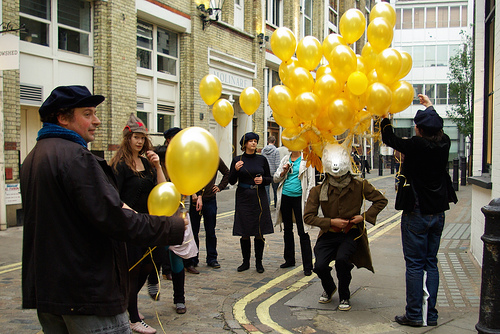 A man with a stag's head waits while people tie balloons to his antlers.