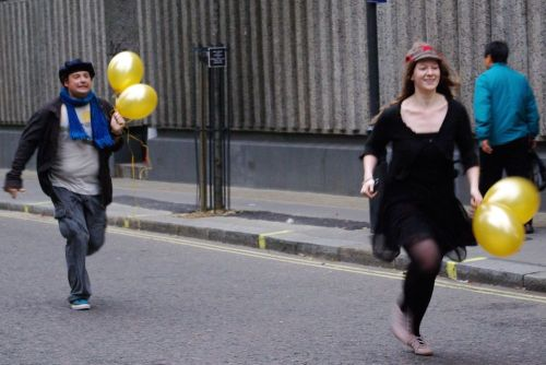 Two players with balloons run along a Soho street.